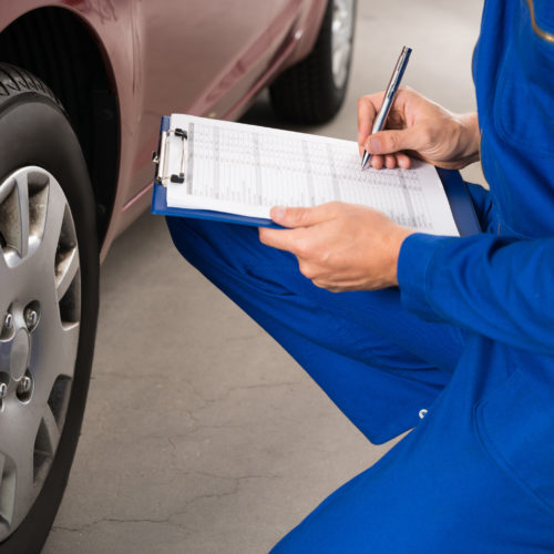 Young Mechanic Writing On Clipboard White Examining Car Wheel