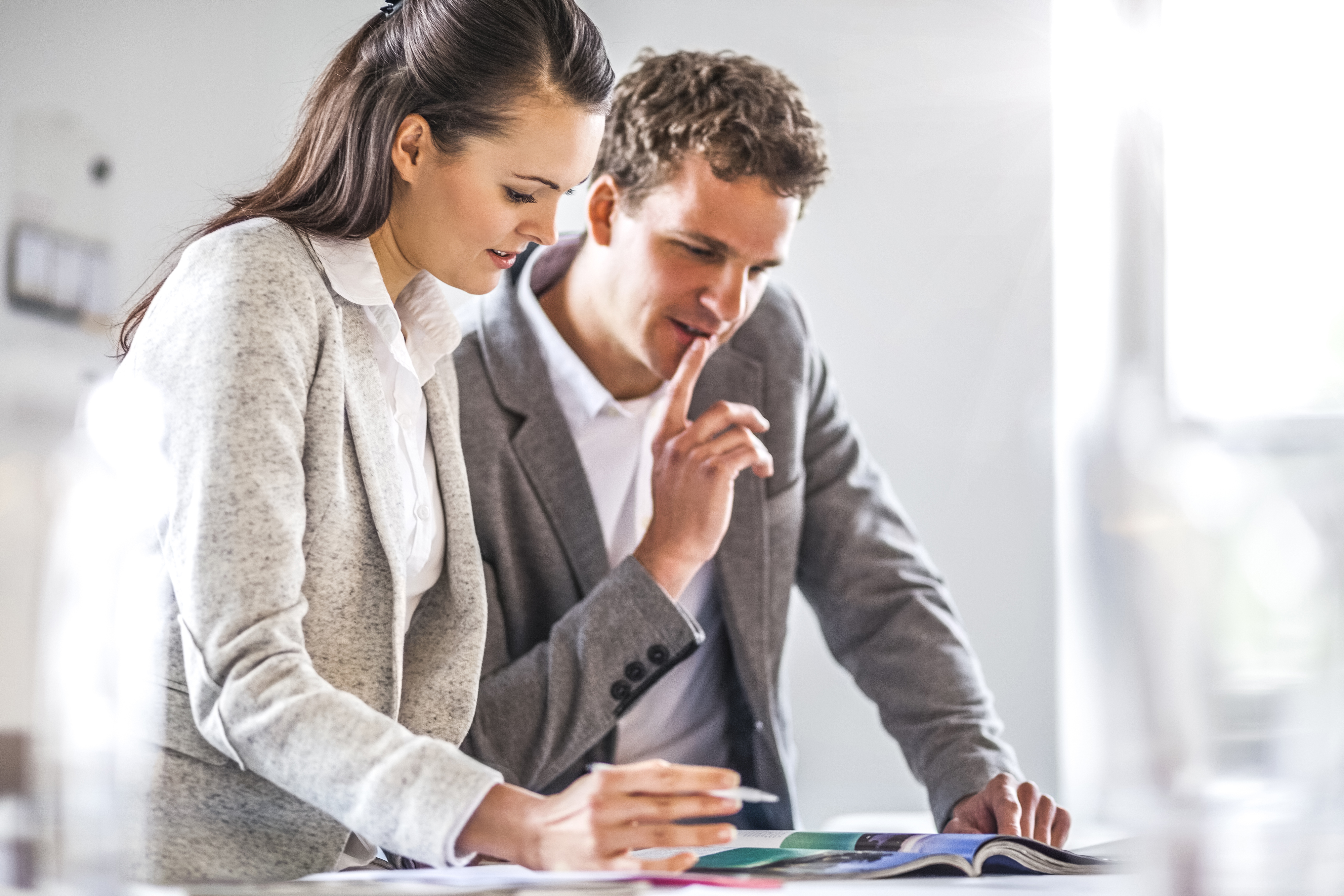 Man and woman reviewing a booklet in the office